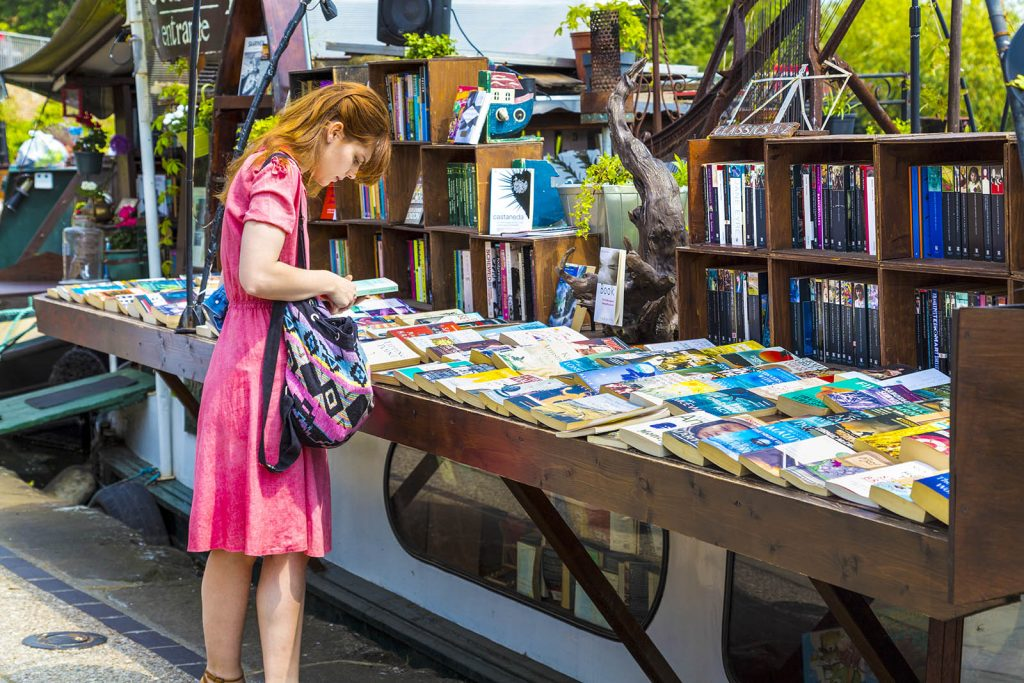 Woman browsing books at Word on Water bookshop barge in Kings Cross