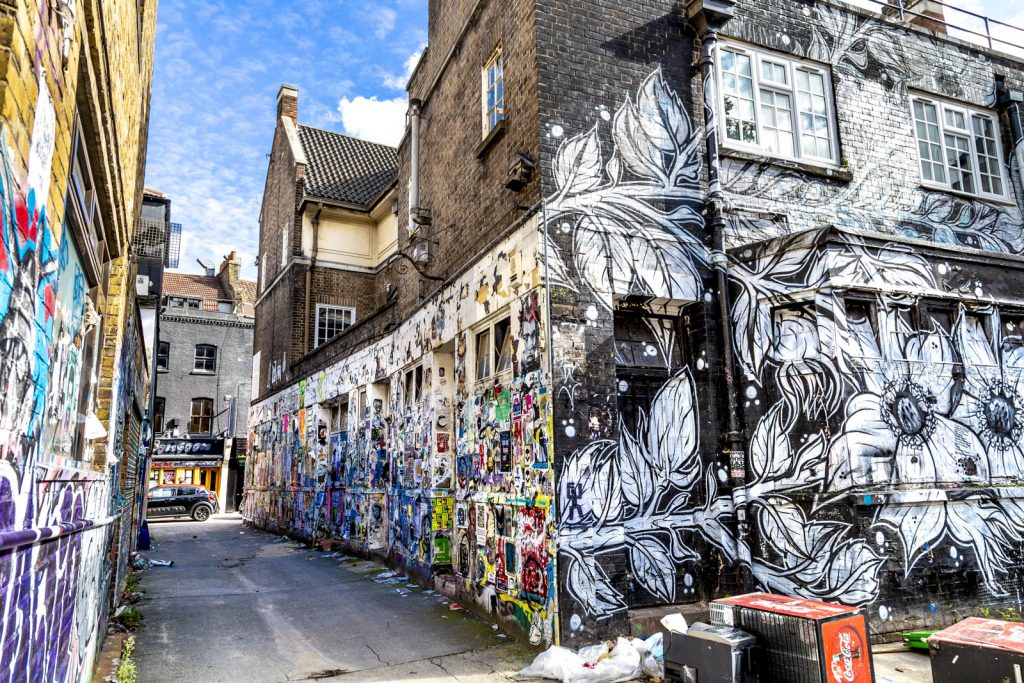 Walls covered in graffiti, posters and artwork by Brick Lane, East London, UK
