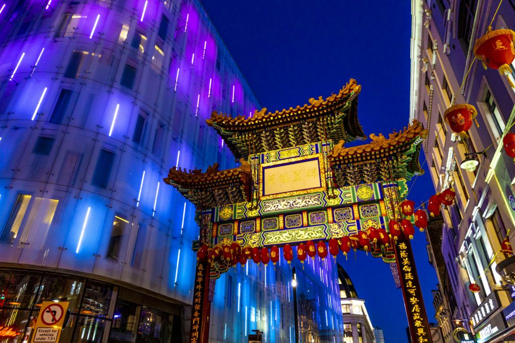 Colourful oriental style gate into Chinatown at night, London, UK