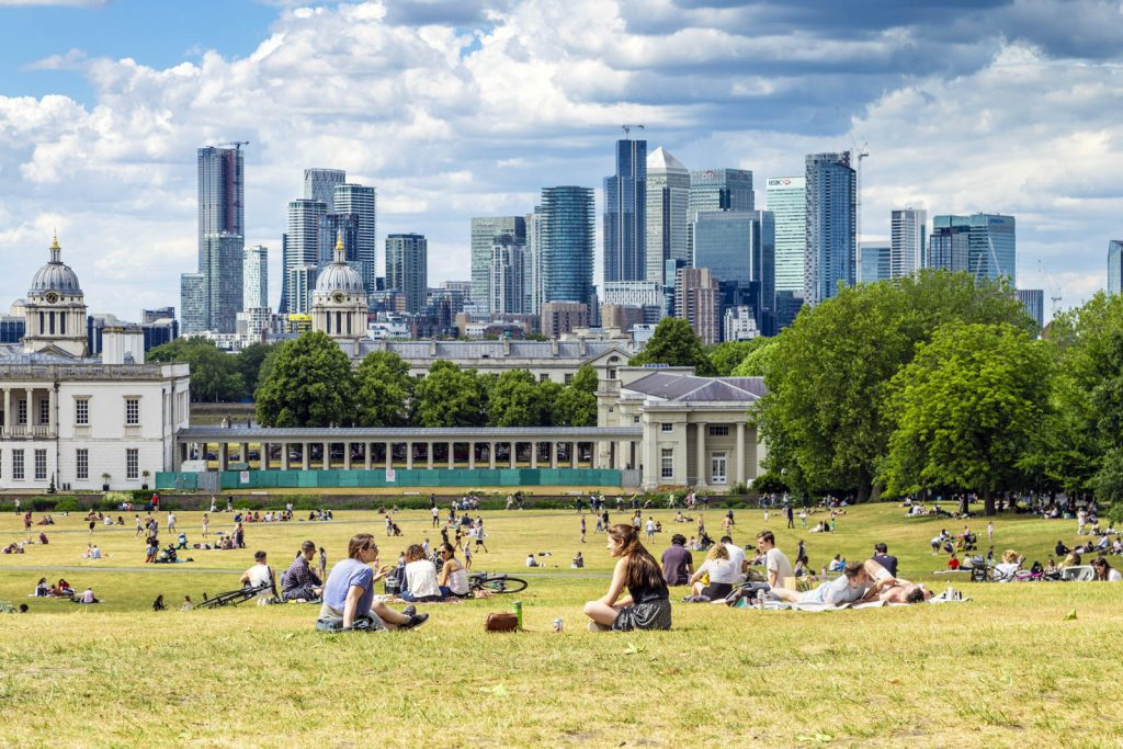 People relaxing in Greenwich Park with scenic views of Canary Wharf, London, UK
