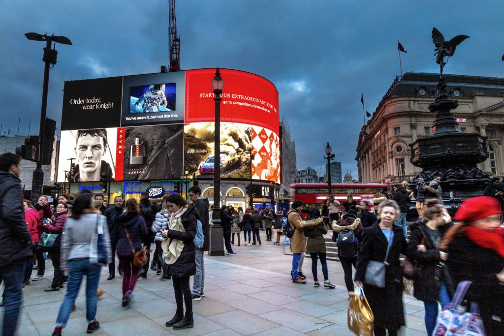 Piccadilly Circus in evening time with the iconic Piccadilly Lights advertising screen in the background, London, UK