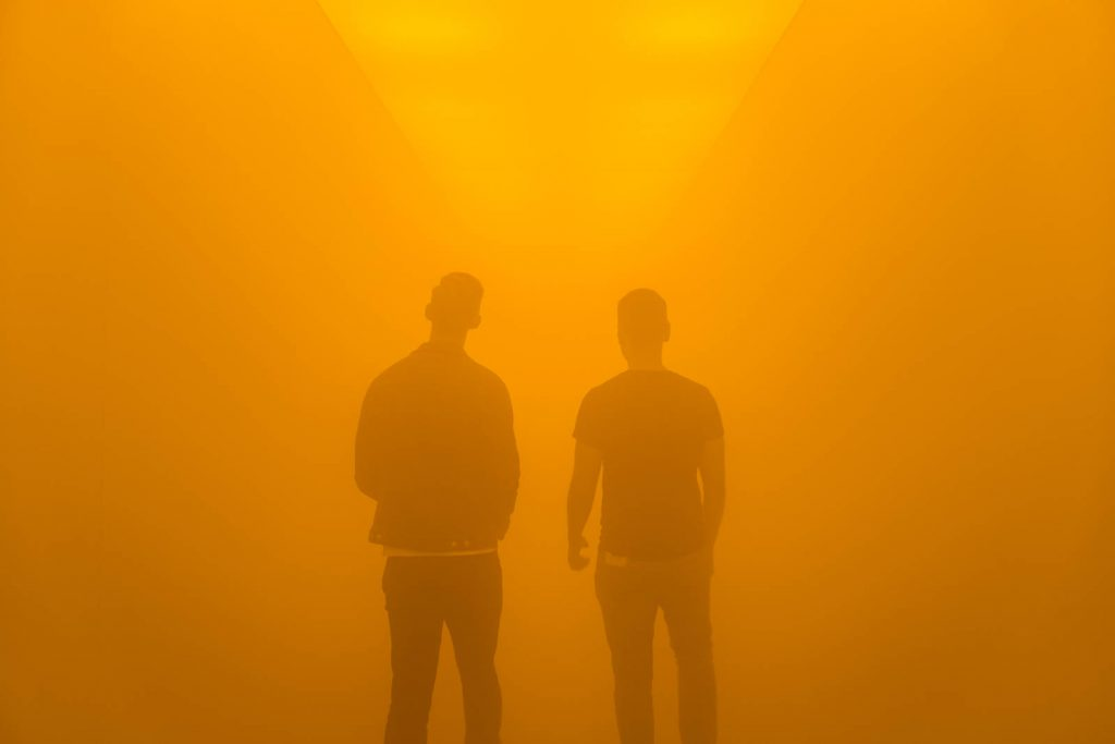 People walking through a fog tunnel during Olafur Eliasson exhibition at the Tate Modern, London, UK
