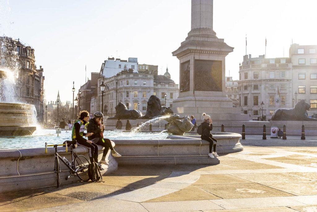 People relaxing Trafalgar Square on a sunny weekend, London, UK