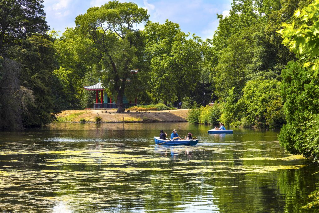 People boating on a lake in Victoria Park, London, UK