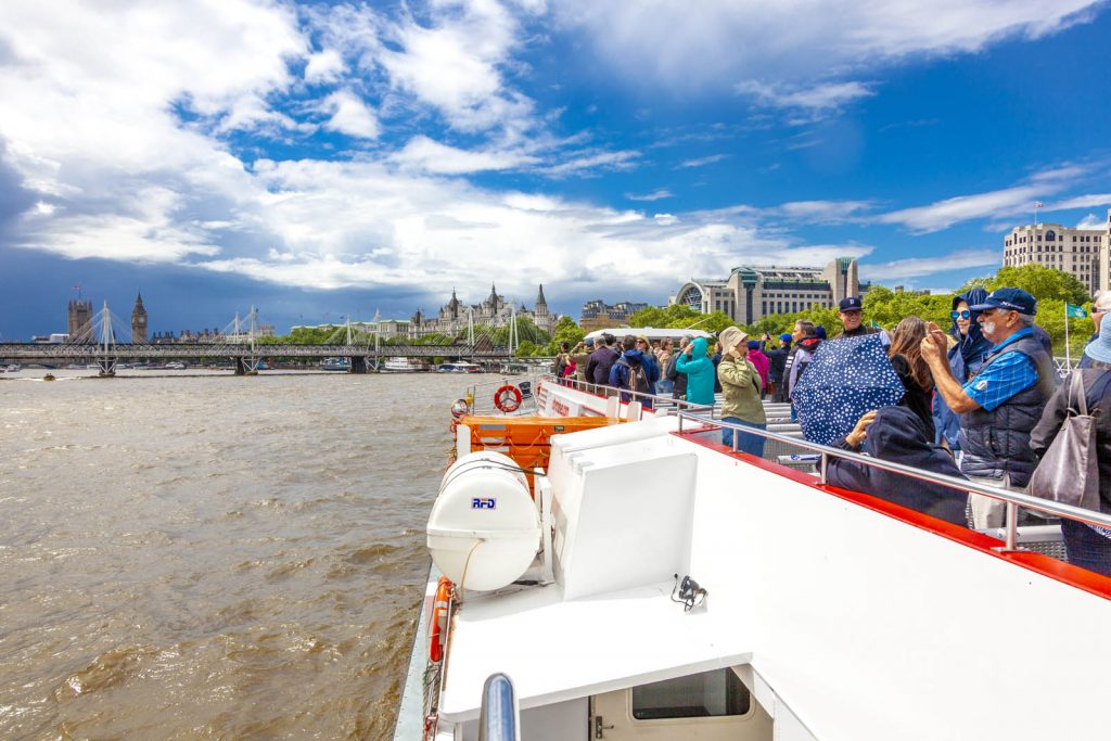 Tourists on a Thames river cruise with Big Ben and Houses of Parliament ahead, London, UK